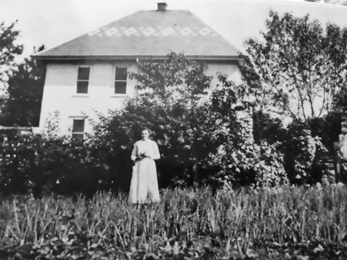 My great grandma in front of the house she grew up in