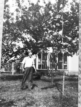 My great grandpa with the farmhouse my grandparents still live in today behind him